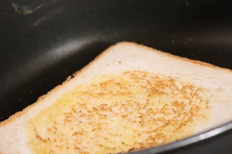 将厚切面包两面涂上黄油。用同一个锅,加入面包用慢火煎至两面金黄色,盛起备用。