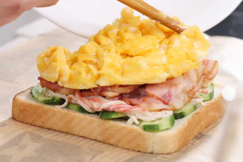 制作培根三明治:在面包上依次铺上奶酪、黃瓜、蟹柳芝麻酱、培根、炒蛋及卷心菜,放上另一块面包,用三明治包装纸包好,对切即成。