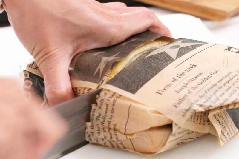 制作火腿三面治:在面包上依次铺上奶酪、黃瓜、蜂糖芥末酱、火腿、炒蛋及卷心菜,放上另一块面包,用三明治包装纸包好,对切即成。